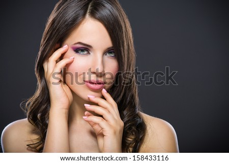 Portrait of beautiful girl touching her face with bright pink makeup on grey background. Concept of beauty and fashion - stock photo