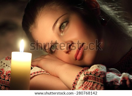 portrait of beautiful girl with a candle. pleasant memories, reflections