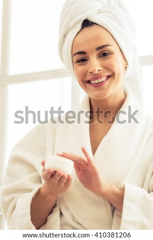 Portrait of beautiful girl with bath towel on her head holding a jar of cream, looking at camera and smiling