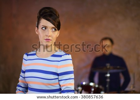 Portrait of beautiful girl with big eyes and dark hair in a striped dress in front of a drummer - stock photo