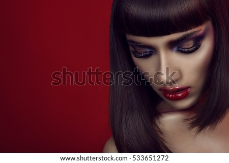 Portrait of beautiful girl with bright colorful provocative make-up, dark smooth shining hair and naked shoulders looking down. Isolated on red background. Copy-space. Close up. Studio shot