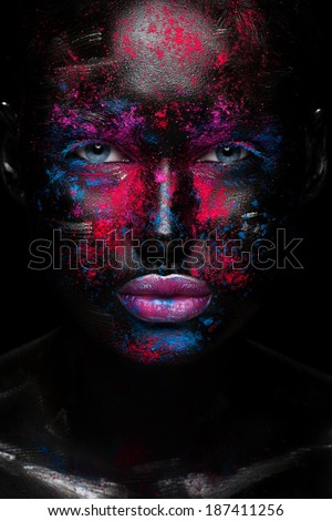 Portrait of beautiful girl with bright fashion art makeup with black face . Over black background  - stock photo