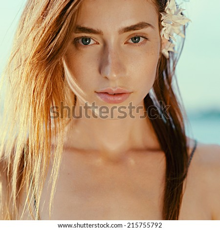 Portrait of beautiful girl with developing hair and pink lips, close up, outdoors
