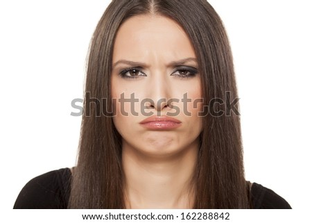 portrait of beautiful girl with dissatisfied gesture posing on white background - stock photo