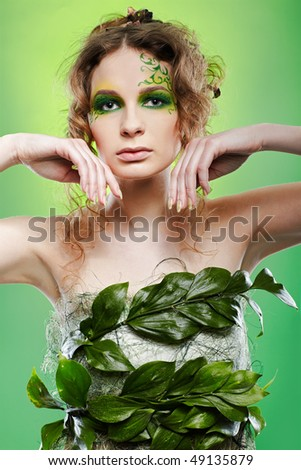 portrait of beautiful girl with fairy theme bodyart posing on green