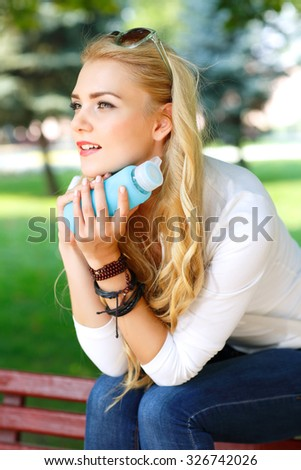 Portrait of beautiful girl with light long hairs in a park. - stock photo