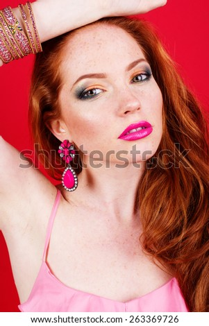 Portrait of beautiful girl with long red hairs is wearing fashion pink jewelry - stock photo