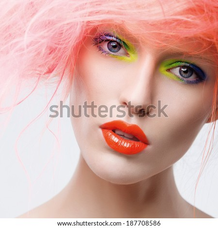 Portrait of beautiful girl with pink hair and colorful make-up in studio - stock photo