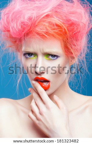 Portrait of beautiful girl with pink hair and colorful make-up, on a blue background