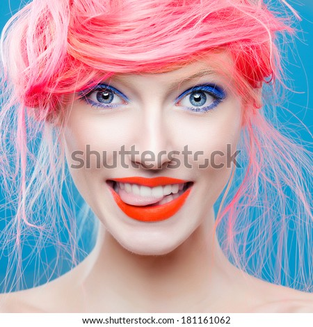 Portrait of beautiful girl with pink hair on a blue background, showing tongue - stock photo
