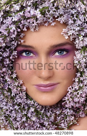 Portrait of beautiful girl with stylish makeup and lilac around her face - stock photo