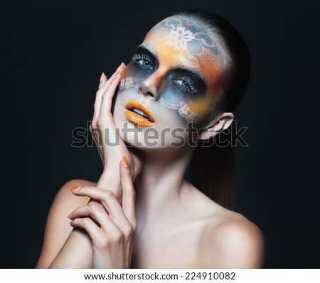 Portrait of beautiful glamor girl with dark eye make-up in the form of lace and orange lips on black - stock photo