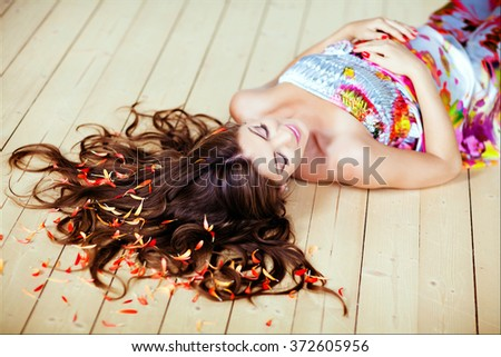 Portrait of beautiful glamor pregnant woman with chic long hair and with closed eyes lying on the floor in the studio - stock photo