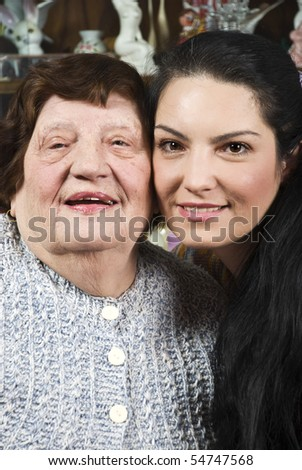 Portrait of beautiful grandma and her granddaughter standing with their faces closed each other and smiling in a living room - stock photo
