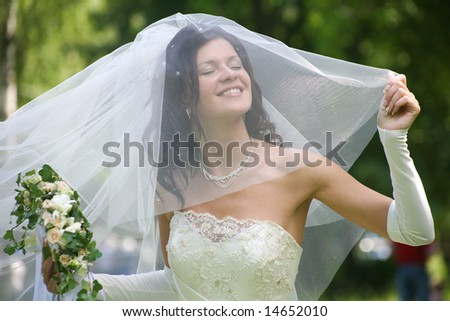 Portrait of beautiful happy bride in wedding wear with bouquet
