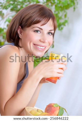 Portrait of beautiful happy brunette woman drinking tasty fresh juice on at home, having breakfast, organic nutrition, healthy lifestyle concept - stock photo
