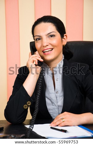Portrait of beautiful happy business woman calling by telephone in her office