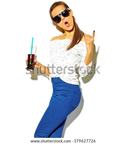 portrait of beautiful happy cute brunette woman girl in casual blue hipster summer clothes with no makeup isolated on white drinking cola from bottle with straw showing rock and roll sign - stock photo