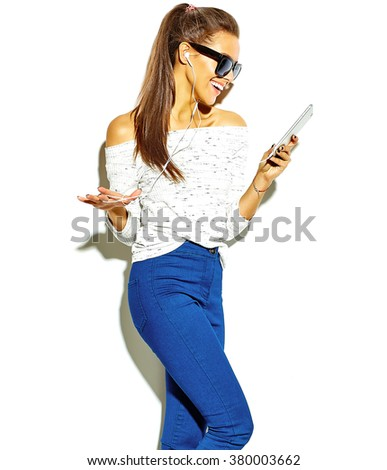 portrait of beautiful happy cute smiling brunette woman girl in casual blue hipster summer clothes with no makeup isolated on white in sunglasses listening music in smartphone with headphones - stock photo