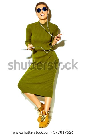 portrait of beautiful happy cute smiling brunette woman girl in casual green hipster summer clothes with no makeup isolated on white in sunglasses listening music in smartphone with headphones - stock photo