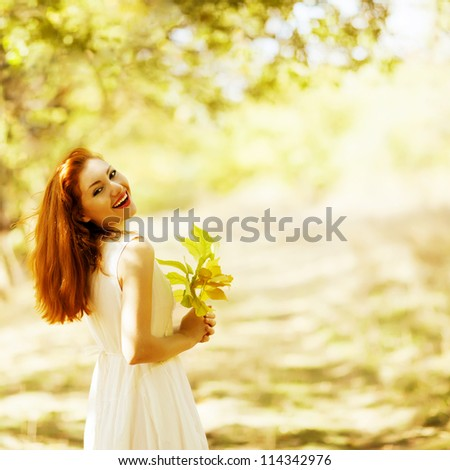 portrait of beautiful happy ginger girl with yellow leaves in the park (forest). outdoor shot - stock photo
