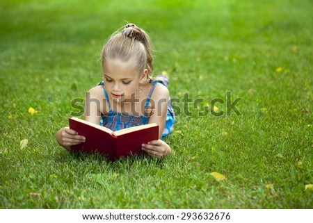 Portrait of beautiful happy little girl reading red book lying on green grass in the summer park - stock photo