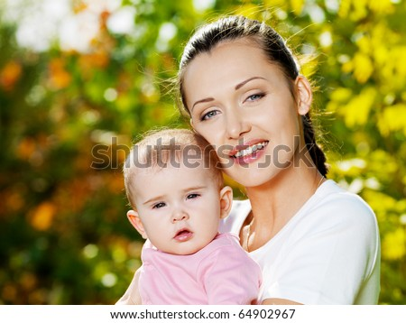 Portrait of beautiful happy mather with baby outdoor, on nature - stock photo