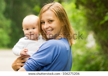 Portrait of beautiful happy smiling mother with baby outdoor - stock photo