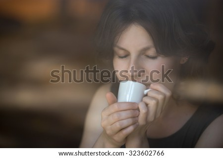 Portrait of beautiful happy smiling young woman sitting in modern cafe holding cup of coffee, enjoying her drink with eyes shut, interior shot through window glass - stock photo