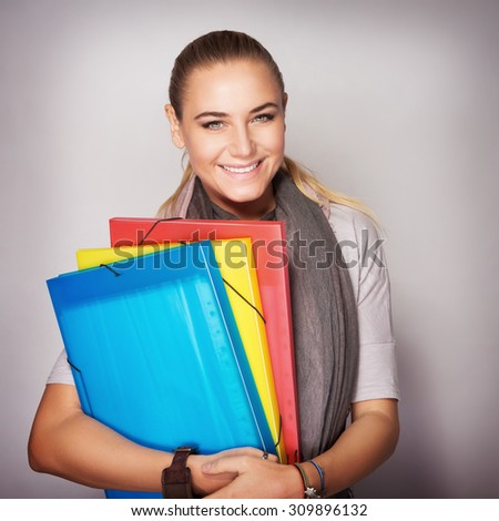 Portrait of beautiful happy student girl with colorful folders in hands over gray background, enjoying start of educational season - stock photo