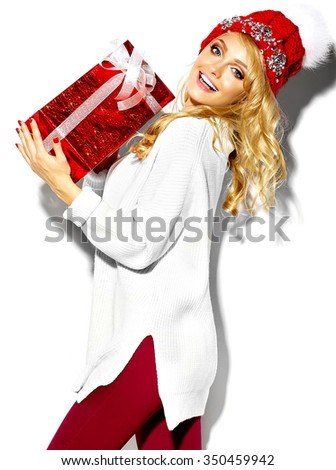 portrait of beautiful happy sweet smiling blonde woman girl holding in her hands big Christmas gift box in casual red hipster winter clothes, in white warm sweater - stock photo
