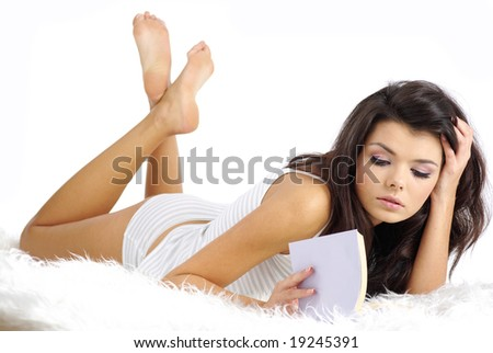 Portrait of beautiful happy woman reading book in bed - stock photo