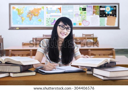 Portrait of beautiful high school student with long hair, studying in the classroom and smiling at the camera - stock photo