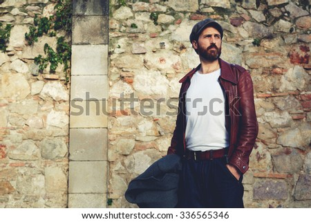 Portrait of beautiful hipster man with trendy look standing near wall background with copy space for your text message or content, fashionable handsome adult male posing outdoors in sunny autumn day  - stock photo