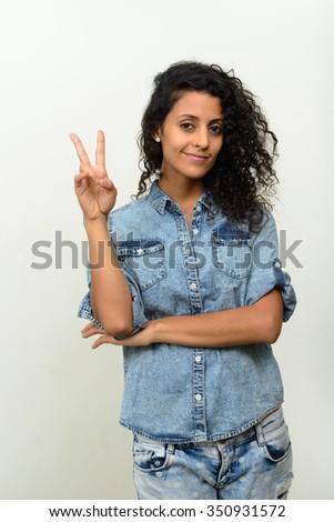 Portrait of beautiful Hispanic woman making peace sign - stock photo