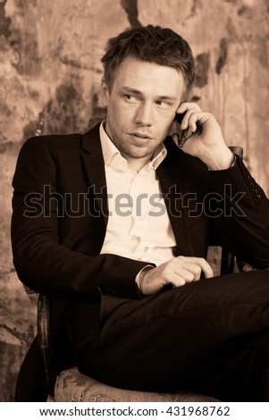 Portrait of beautiful imposing man on vintage wall background. Sits on vintage chair and talking on mobile phone. Blond. Dressed in classic formal suit.  Sepia colour graded.