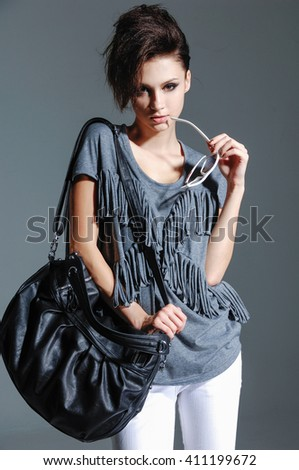 Portrait of beautiful in sunglasses with bag posing on gray background - stock photo