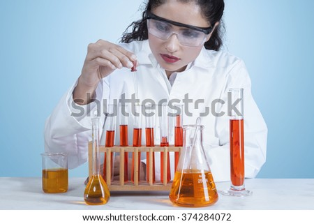 Portrait of beautiful indian scientist doing research with test tube while wearing coat and glasses - stock photo