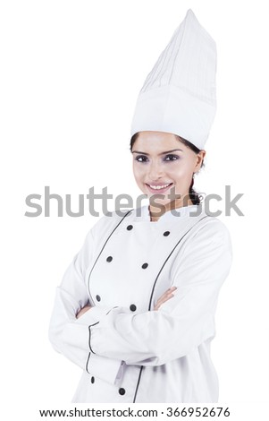 Portrait of beautiful indian woman chef standing in the studio while wearing work wear and crossed hands - stock photo