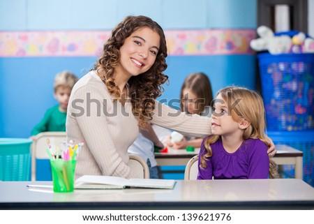 Portrait of beautiful kindergarten teacher with little girl sitting at desk in classroom - stock photo