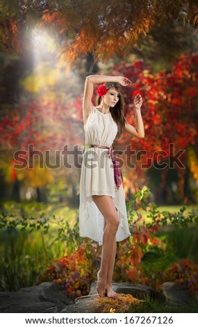 Portrait of beautiful lady in the forest.  Girl with fairy look in autumnal shoot.  Girl with Autumnal Make up and Hair style.  Romantic woman with short white dress and red flower in her hair posing - stock photo