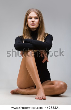 Portrait of beautiful lady sitting on the floor in the studio - stock photo