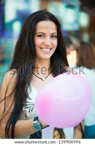 Portrait of beautiful latin woman smiling at mall with baloon - stock photo