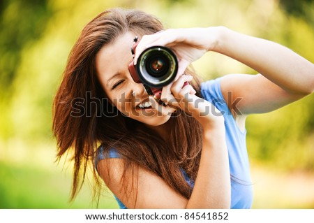 Portrait of beautiful laughing brunette girl wearing blue t-shirt, making photos at summer green park. - stock photo
