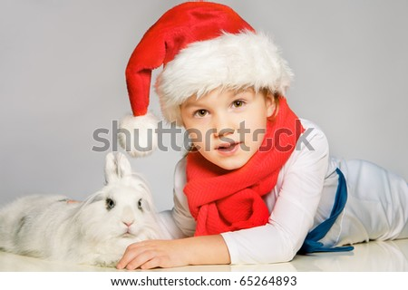 Portrait of beautiful little boy in New Year costume with white bunny