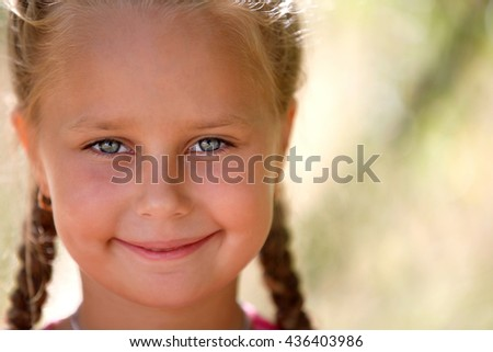 Portrait of beautiful little girl, against background of summer park - stock photo