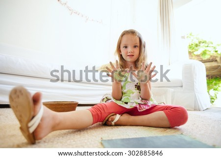 Portrait of beautiful little girl having fun while painting. Schoolgirl sitting on floor at home showing her painted palms. - stock photo