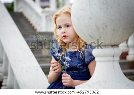 Portrait of beautiful little girl in a Park near the white stairs