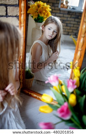 Portrait of beautiful little girl in front of a mirror with flowers