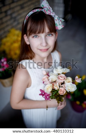 Portrait of beautiful little girl in the Studio with flowers